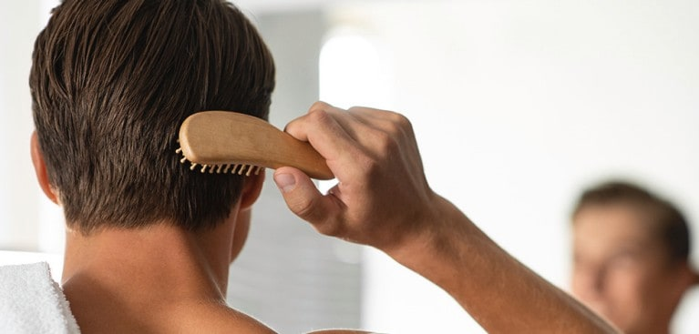 Man brushing hair while looking in the mirror