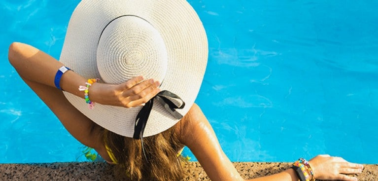 Women with sunhat lounging by the pool