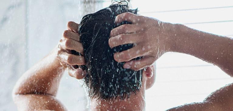 Pria mencuci rambut di kamar mandi