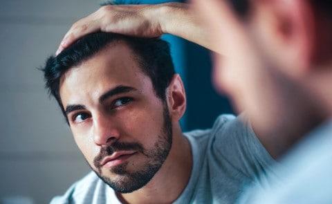 Man checking hairline in mirror
